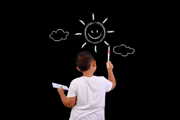 Мальчик рисует небо и солнце на доске Бесплатные Фотографии