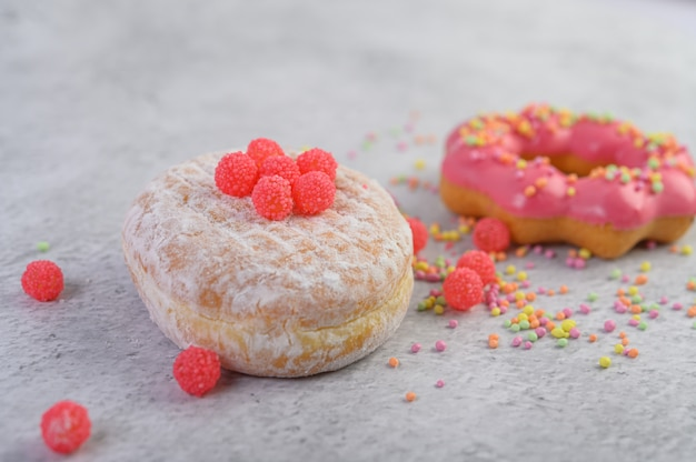 Пончики посыпать сахарной пудрой и конфеты на белой поверхности. Бесплатные Фотографии