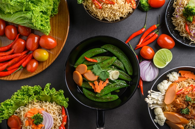 フライパンでエンドウ豆を炒め、ボウルに黒セメントの表面に食材を使ったスパイシーな麺。 無料写真