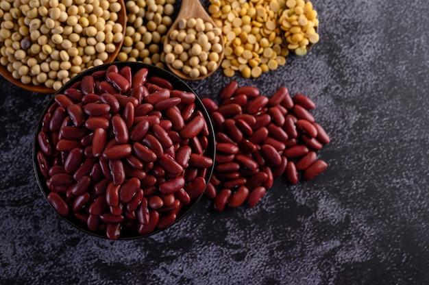 Красная фасоль в деревянной миске на черном цементном полу. Бесплатные Фотографии
