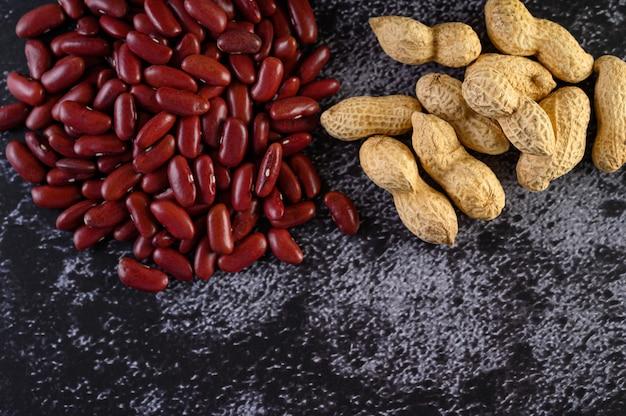 Арахис и красная фасоль на черном цементном полу. Бесплатные Фотографии