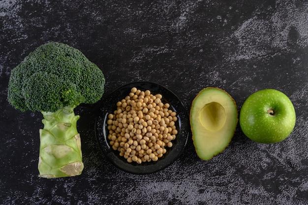 黒いセメントの床にブロッコリー、大豆、リンゴ、アボカド。 無料写真