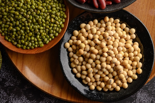 黒いセメントの床のプレート上の緑豆と大豆。 無料写真