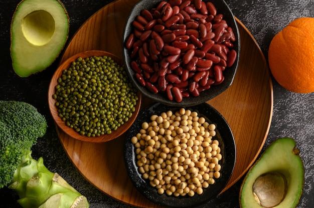 黒いセメントの床にマメ科植物と果物。 無料写真