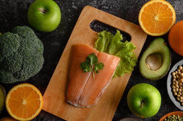 木製のまな板の上のマメ科植物、果物、およびサケの魚片。 無料写真