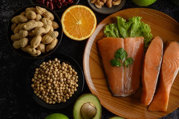 木の板にマメ科植物、フルーツ、サーモンの部分。 無料写真