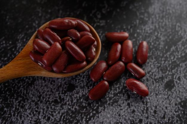 Красная фасоль в деревянной ложкой на черном цементном полу. Бесплатные Фотографии