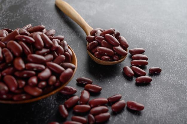 Красная фасоль в деревянной миске и деревянной ложкой на черном цементном полу. Бесплатные Фотографии