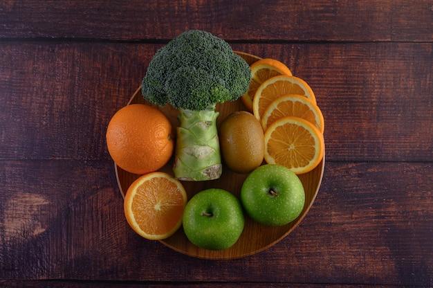 木の板にオレンジ色の部分、リンゴ、キウイ、ブロッコリー。 無料写真