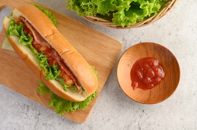 木製まな板の上のレタスとトマトソースのホットドッグ 無料写真