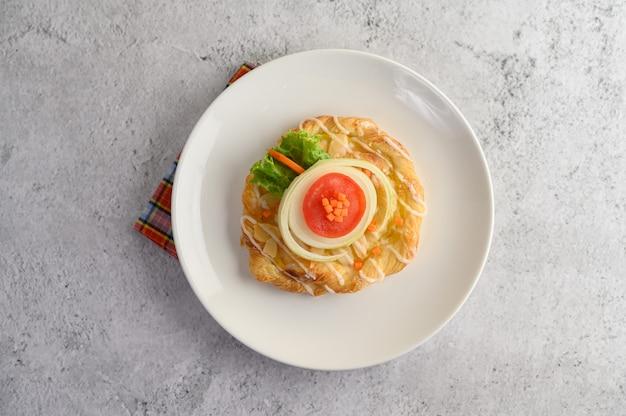 白い皿にアーモンドツイストパンで食欲をそそる 無料写真