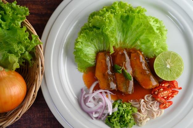 イワシのピリ辛サラダ、白い皿にトマトソース 無料写真