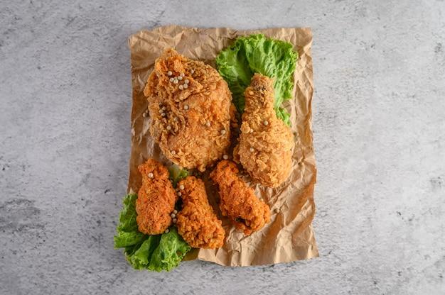 茶色の紙の上にサラダと唐辛子の種子を振りかけたカリカリのフライドチキン。 無料写真