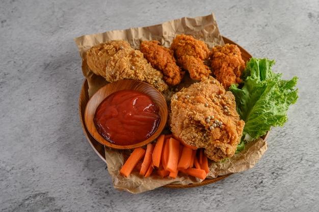 Хрустящая жареная курица на деревянной тарелке с томатным соусом и морковью Бесплатные Фотографии