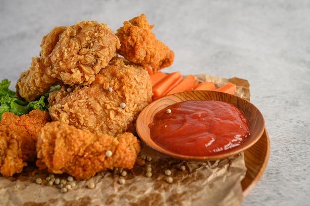 トマトソースがけの皿にカリカリのフライドチキン 無料写真