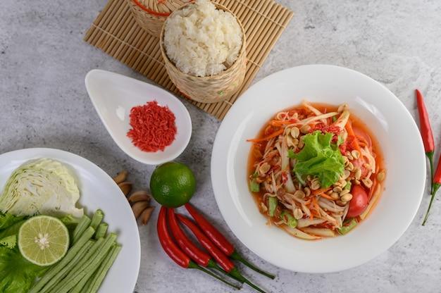 Тайский салат из папайи в белой тарелке с клейким рисом в плетеной корзине из бамбука и сушеными креветками Бесплатные Фотографии