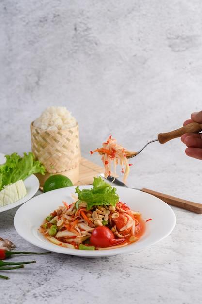 もち米と干しエビの白いプレートのタイのパパイヤサラダ 無料写真