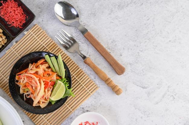 Тайский салат из папайи в белой тарелке с клейким рисом и сушеными креветками Бесплатные Фотографии