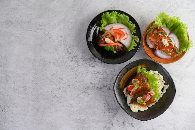 Аппетитная консервированная сардина в остром соусе в черной керамической миске Бесплатные Фотографии