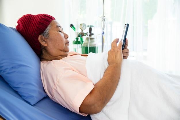 高齢女性は病院の患者のベッドでスマートフォンを使用 無料写真