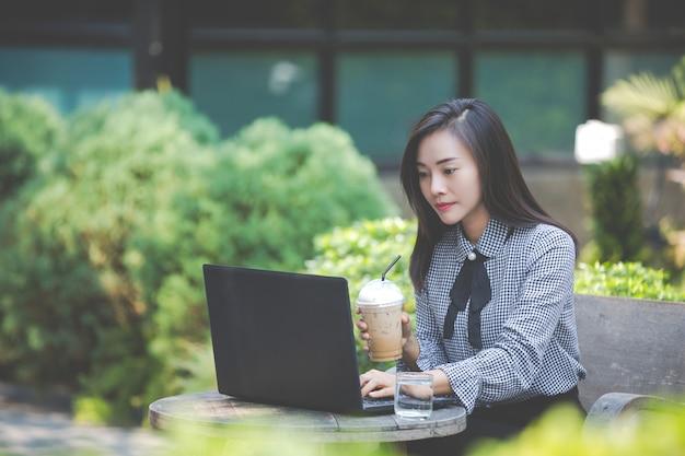 カフェのラップトップに取り組んでいると、コーヒーを飲む女性 無料写真