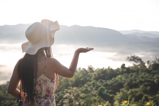 山の空きスペースで手を上げる女性 無料写真