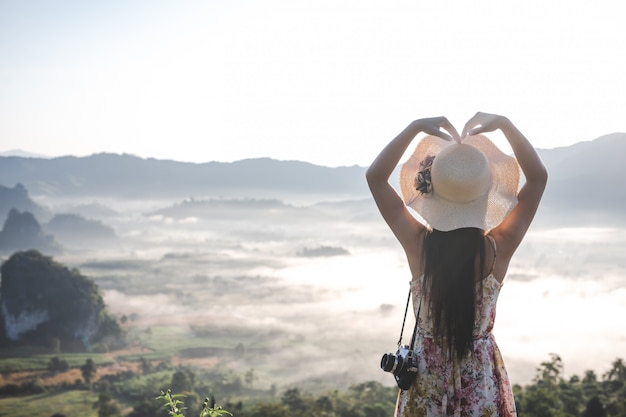 女性は山の視点でハート型のジェスチャーを見せます。 無料写真