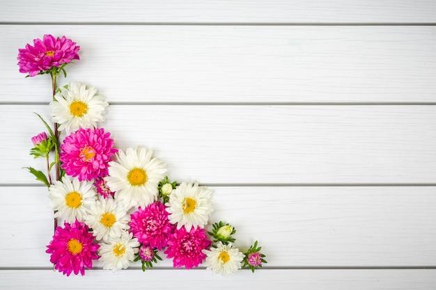 白い木製の背景に白と紫のピンクのデイジー 無料写真