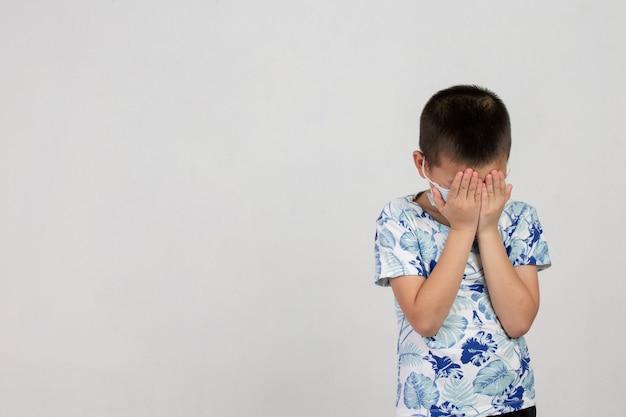 Мальчик в маске позирует на белом фоне Бесплатные Фотографии