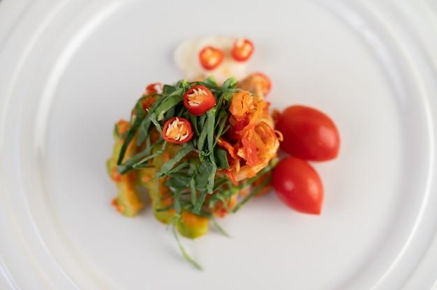 チリ、カフィアライムの葉、ゴーヤ、トマトが白い皿の上に重ねられています。 無料写真