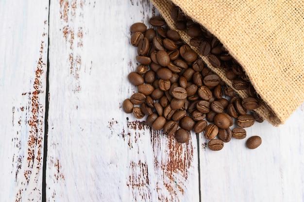 Кофейные зерна в мешках пеньки на белом деревянном столе. Бесплатные Фотографии
