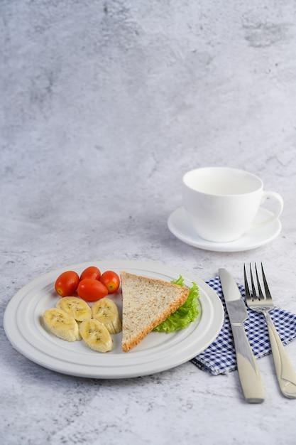 フォークとナイフで白い皿にパン、バナナ、トマト。 無料写真