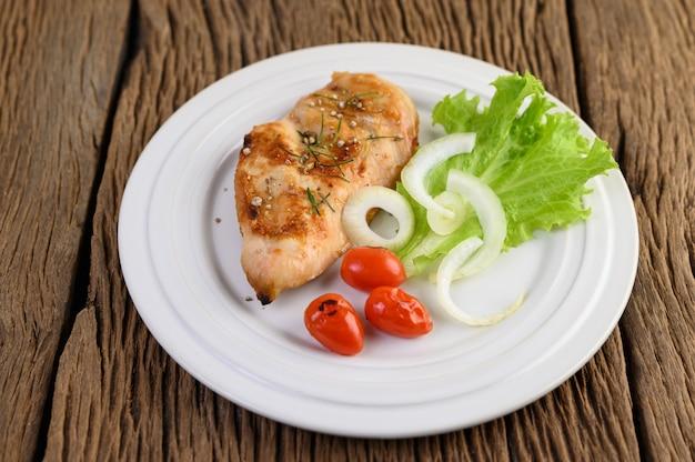 トマト、サラダ、タマネギの白い皿に鶏のグリル。 無料写真