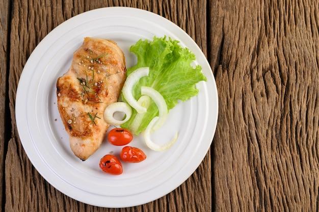 Жареная курица на белой тарелке с помидорами, салатом и луком. Бесплатные Фотографии