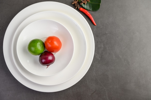 Лайм, красный лук и помидоры на белой тарелке. Бесплатные Фотографии