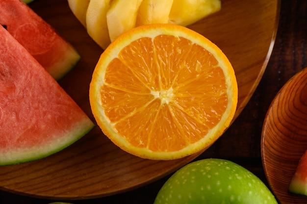 スイカ、オレンジ、パイナップルをりんごと木の板に切ります。 無料写真