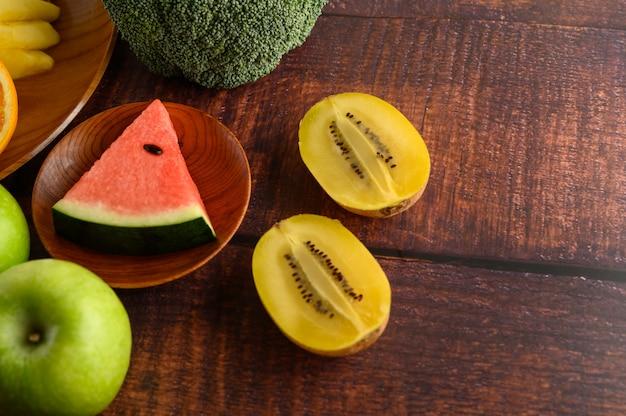 スイカ、パイナップル、キビ、リンゴとブロッコリーで木の板にカットします。 無料写真