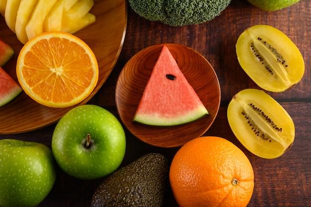スイカ、オレンジ、パイナップル、キウイは、木製のプレートと木製のテーブルにリンゴとブロッコリーのスライスにカットしました。 無料写真