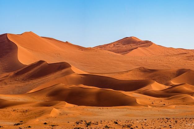 ナミビアのナミブナウクルフト国立公園ソススフレイのナミブ砂漠にあるオレンジ色の砂丘のオレンジ色の砂の美しい風景。 無料写真