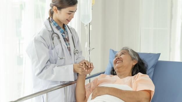 医師は病院-シニア女性の医療とヘルスケアの概念で高齢者のシニア女性患者を奨励するために手を握る 無料写真