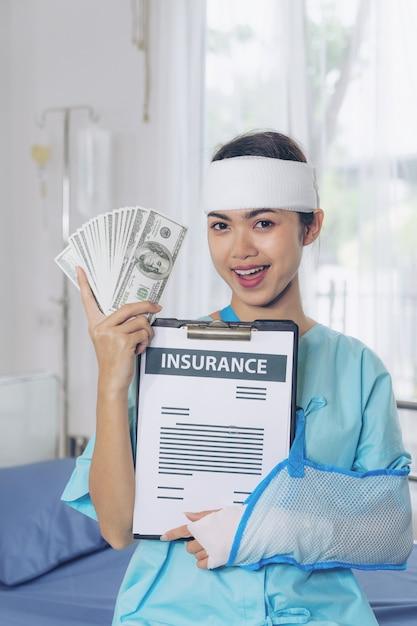 私たちのドル札を保持している病院の車椅子の事故患者の傷害の女性は保険会社からの保険金を得ることから幸せを感じます-医療コンセプト 無料写真