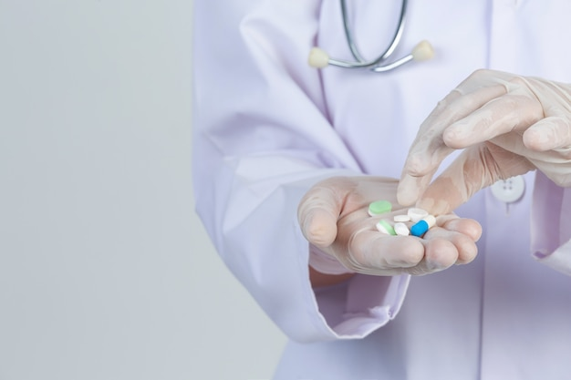 美しい若い医者は灰色の壁にゴム手袋で薬を押しながらマスクを着ています。 無料写真