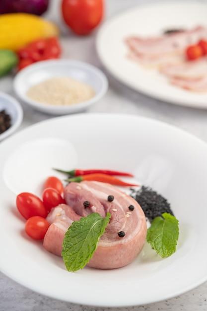 コショウの種のトマトとスパイスが入った白い皿に豚バラ肉。 無料写真