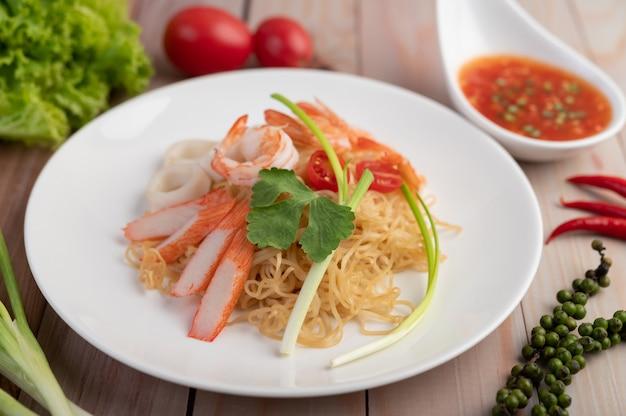 海老と蟹の棒が入ったインスタント麺を白い皿に炒めます。 無料写真