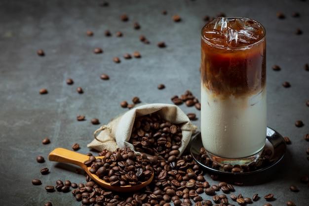 背の高いグラスにアイスコーヒーを注ぎ、クリームをトッピングして、コーヒー豆で飾られたアイスコーヒーを飲みます。 無料写真