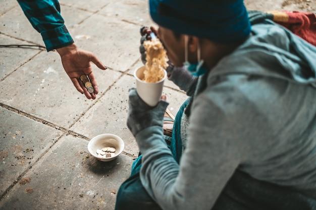 乞食たちは布に包まれて麺を食べていました。 無料写真