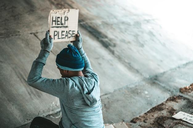 Нищие сидят под мостом с табличкой, помогите пожалуйста. Бесплатные Фотографии