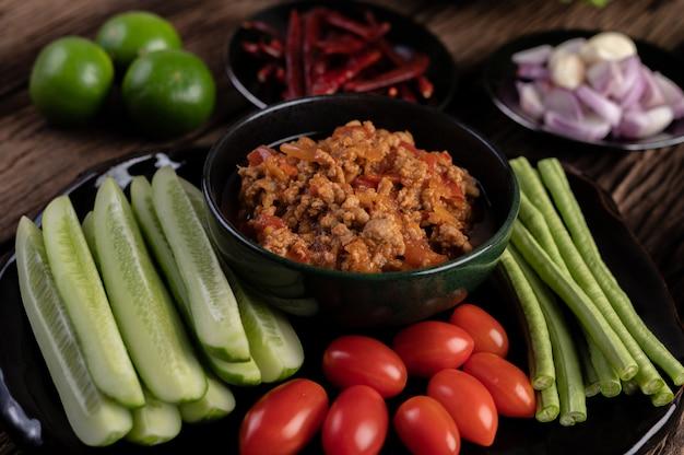 きゅうり、長豆、トマト、おかずが入った黒いボウルの甘い豚肉 無料写真