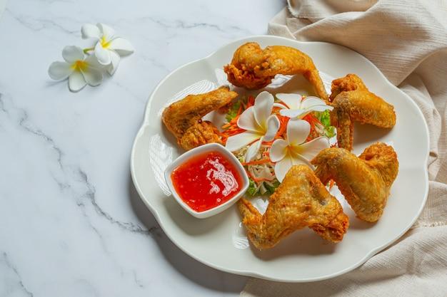 Жареные крылышки с рыбным соусом, красиво украшенные и поданные. Бесплатные Фотографии