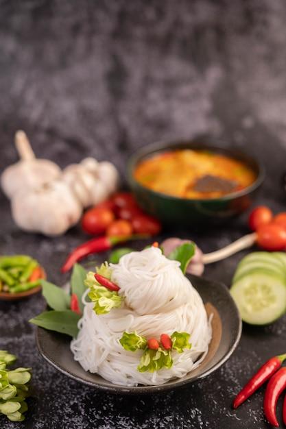 Куриное карри в черной чашке с рисовой лапшой. Бесплатные Фотографии